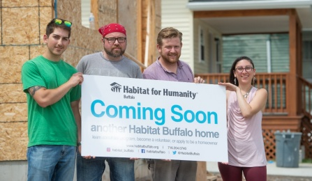 "Group of students holding sign for Habitat for Humanity, ""coming soon, another Habitat Buffalo Home.""."