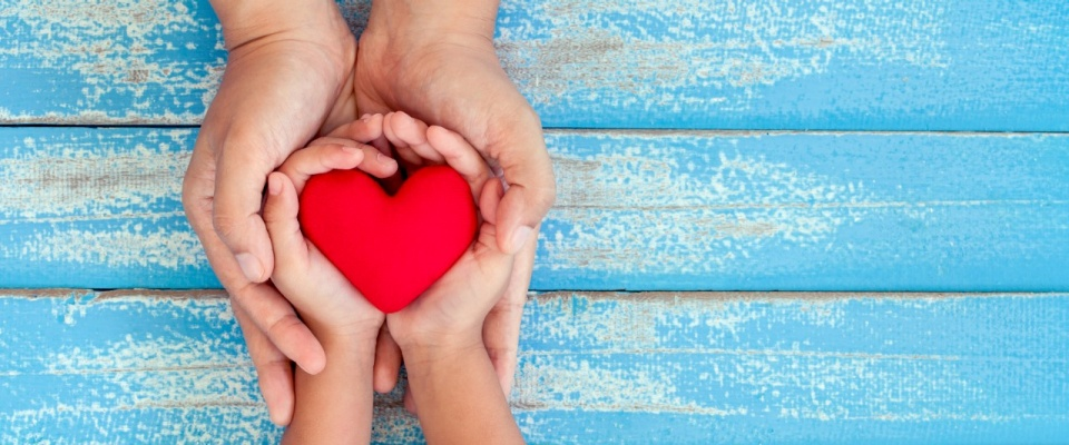 child and parent holding heart in heands
