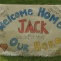 "sign that says ""Welcome home, Jack! Our Hero!""."