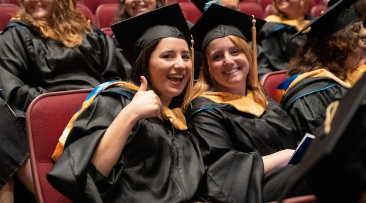 students giving thumbs up at commencement.
